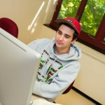 Male student at computer in red baseball cap